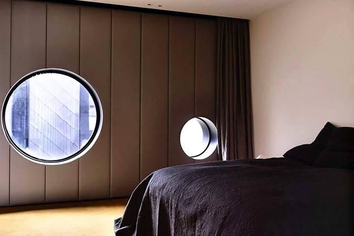 два круглых окна в спальне дома